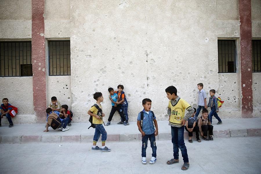 تلاميذ في باحة المدرسة بمدينة دوما وقد ظهر آثار القصف وإطلاق الرصاص على الجدران