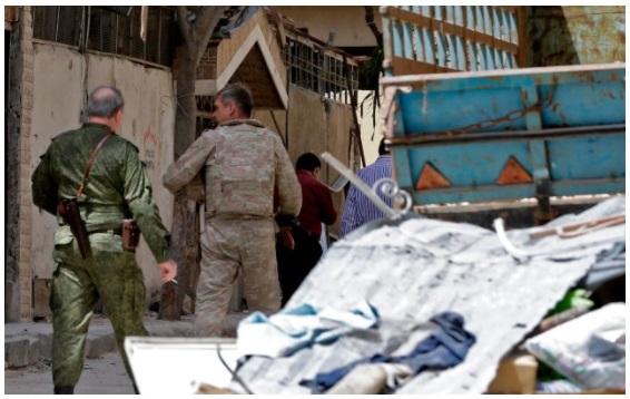 أفراد من الشرطة العسكرية الروسية يسيرون وسط الدمار في مدينة دوما بالغوطة الشرقية