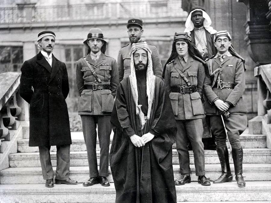 الملك فيصل خلال مؤتمر فرساي 1919 وخلفه من اليمين تحسين قدري وأحد مرافقي الملك ولورانس والنقيب بيساني ونوري السعيد ورستم حيدر