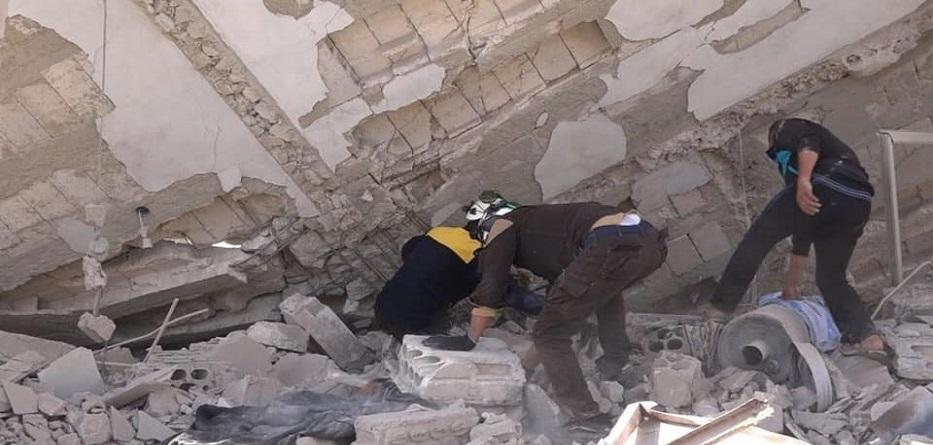 متطوعو الدفاع المدني السوري يحاولون إنقاذ عالقين تحت أنقاض مبنى تعرض للقصف في جبالا بريف إدلب
